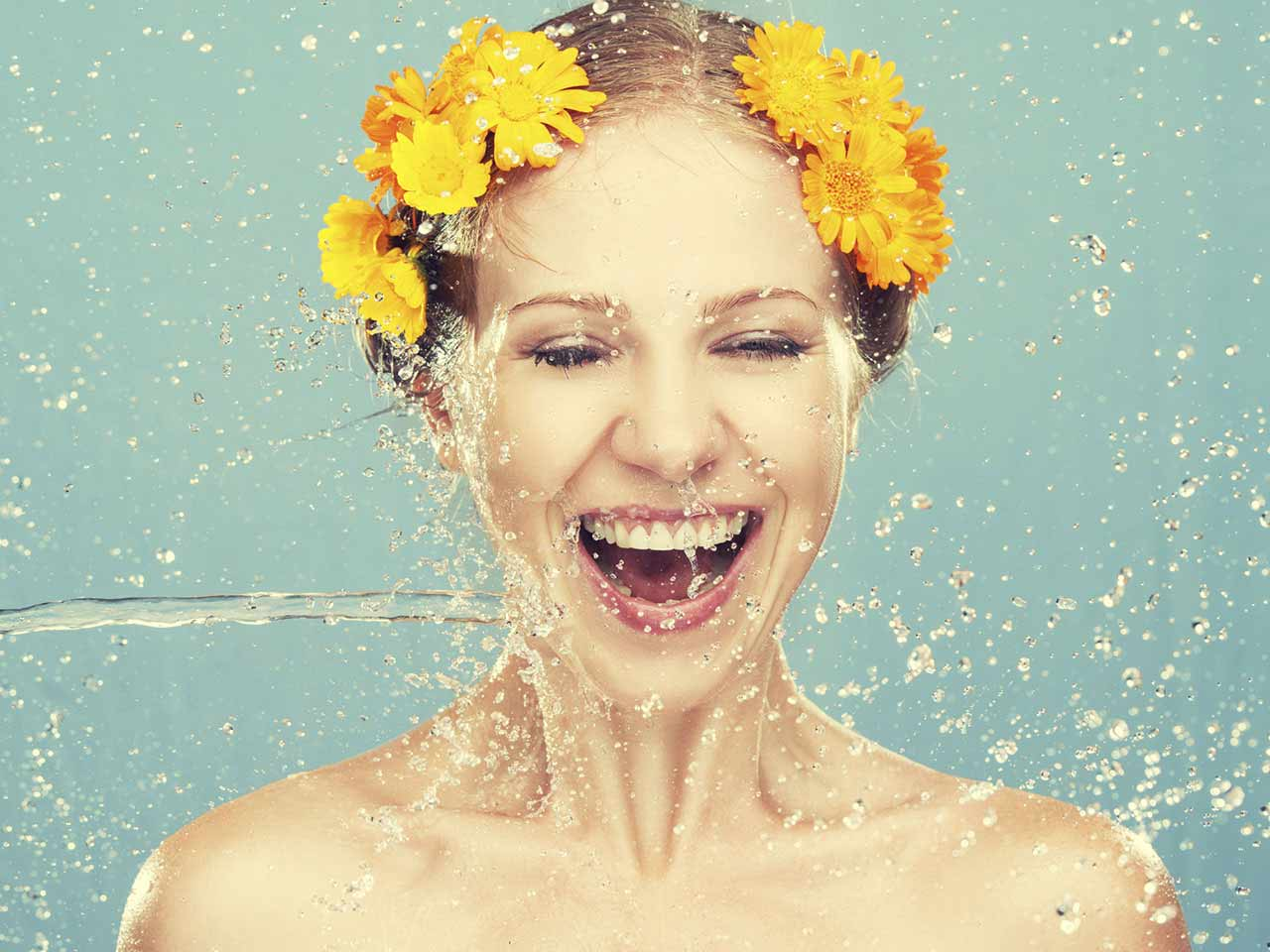 Woman being showered with water as part of her skin care routine
