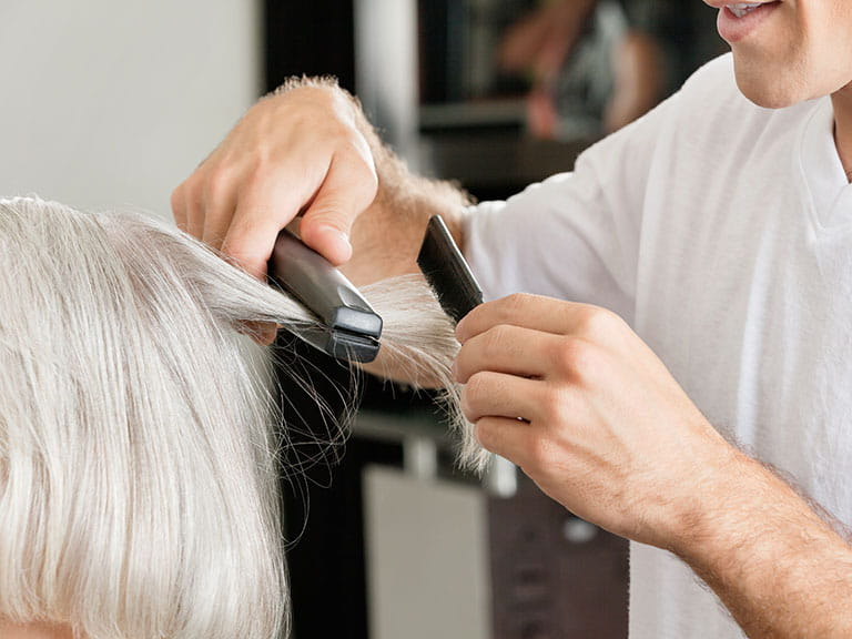 Mature woman having hair straightened