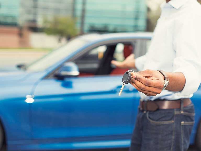 A man holds car keys and gestures to a car to represent a successful sale
