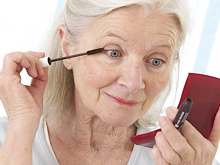 An older lady applies make-up