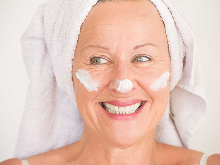 An older lady looks after her skin and avoids wrinkles by applying sun tan lotion