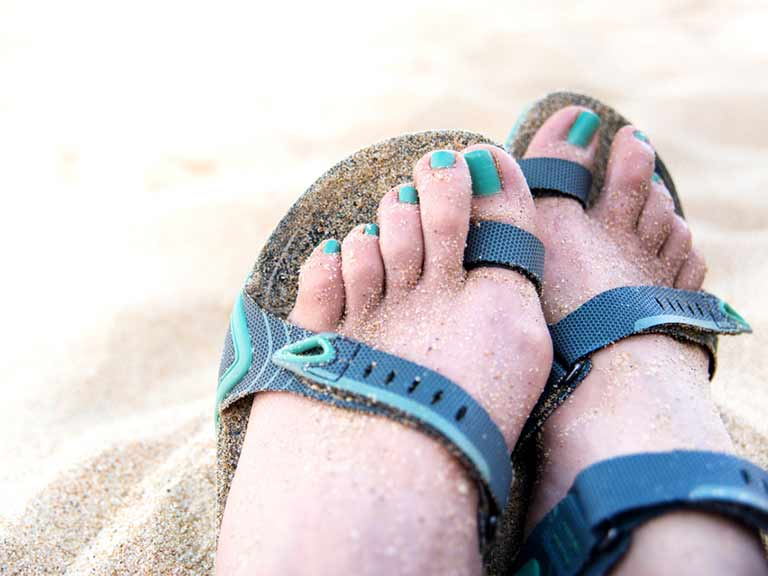 Happy feet in sandals on a sandy beach