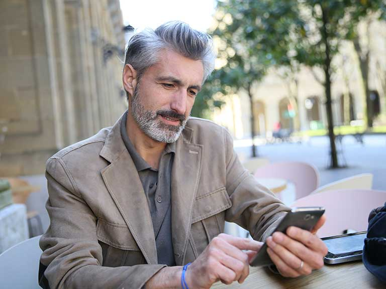 Mature grey haired man using mobile