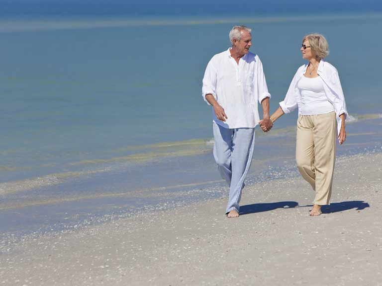 A couple walk along a beach in the sunshine - but have they applied enough sun protection for their hair?
