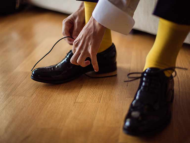 A man ties his shoes with yellow socks making a splash of colour