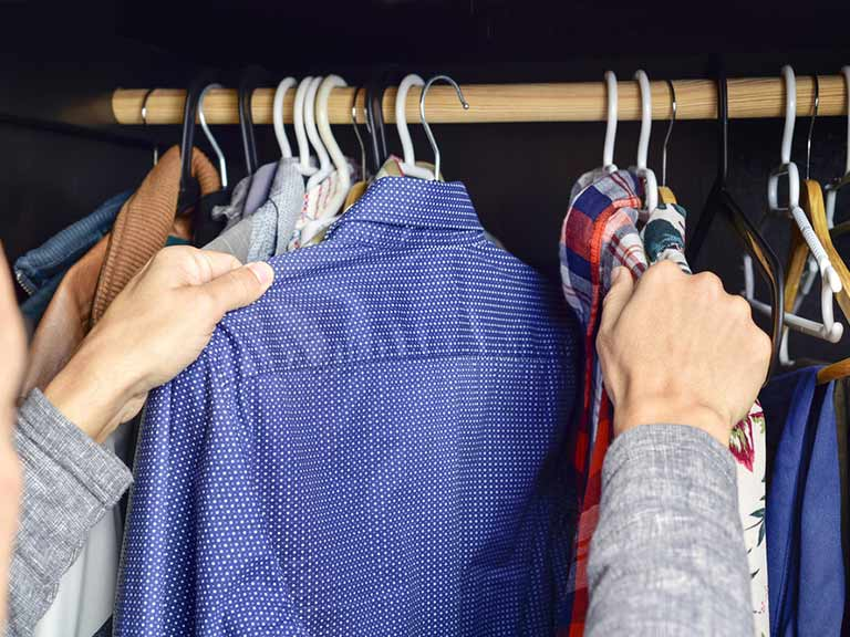 A man reaches for a tailored shirt in his wardrobe