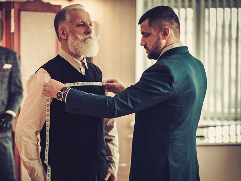 A man gets measured for his bespoke tailored suit