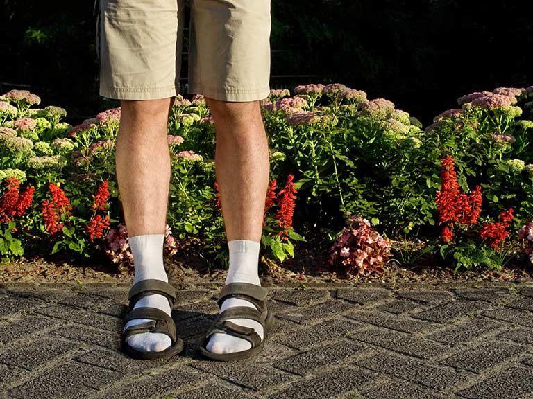A man wears socks under sandals and wonders why no one is standing next to him
