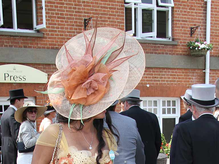 A woman wearing a big hat attends Royal Ascot