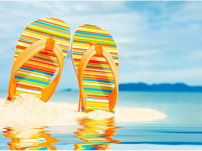 A pair of stripey flip flops stand on a beach