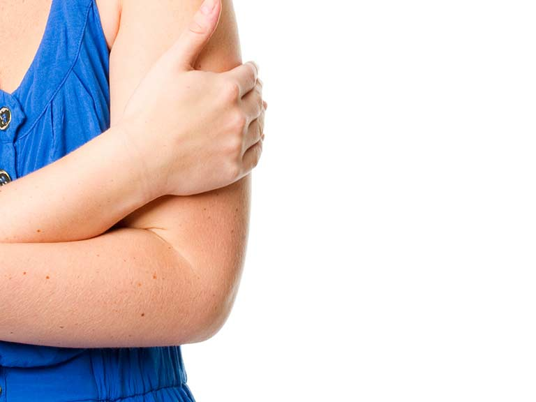 A woman hides her upper arms