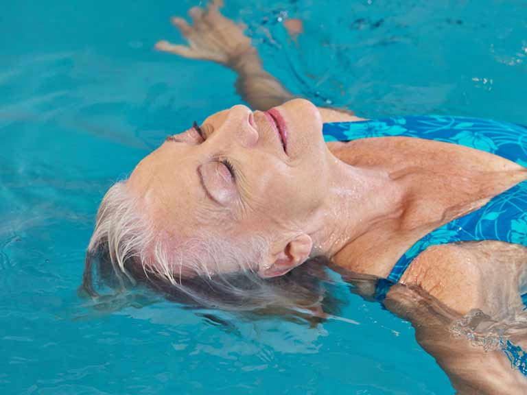 A woman swims happily in a pool knowing her hair has been pre-treated