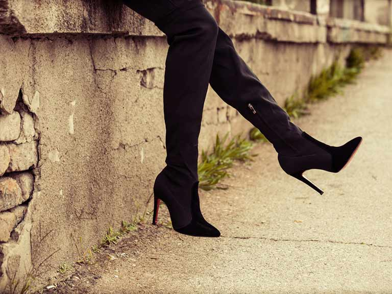 A woman wearing high heeled boots take a quick break