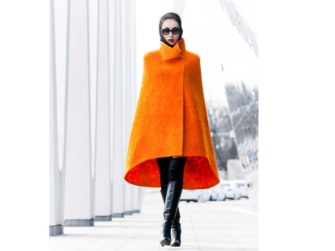 Stylish woman wearing an orange winter coat and black boots