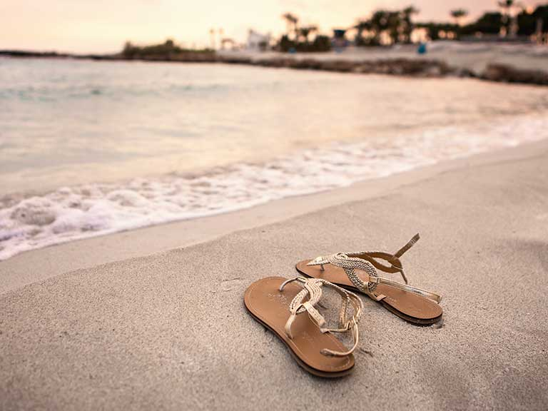 A pair of summer sandals left by the sea