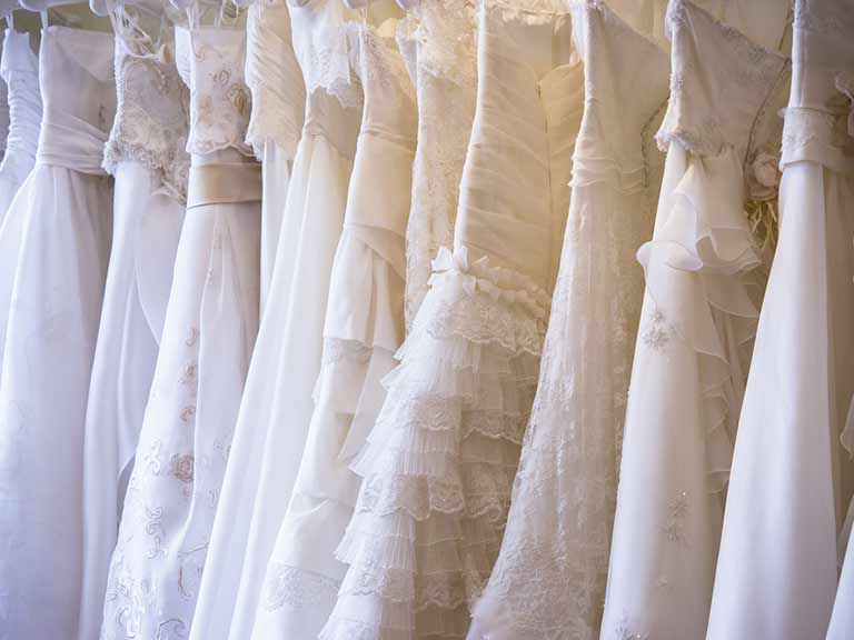 Wedding dresses hanging on a rail in a bridal boutique