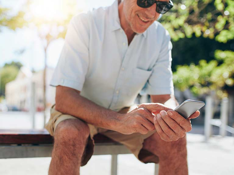 An older man enjoys the apps on his smartphone