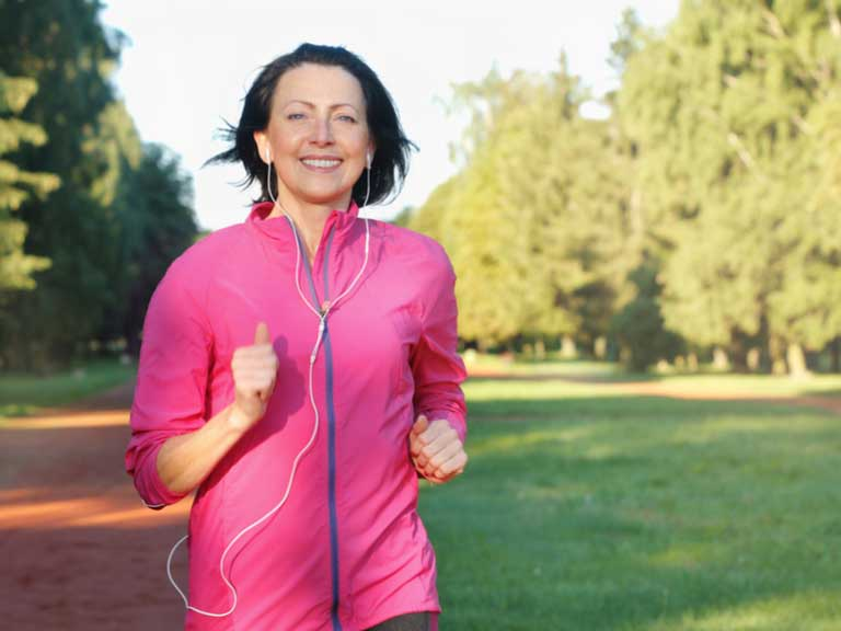 Smiling older lady jogging in a park