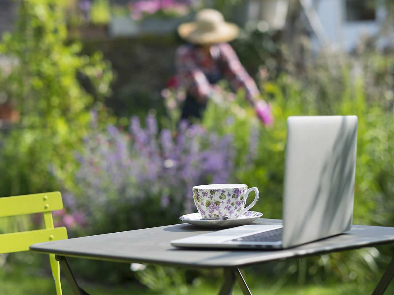 Lady gardening with laptop in foreground