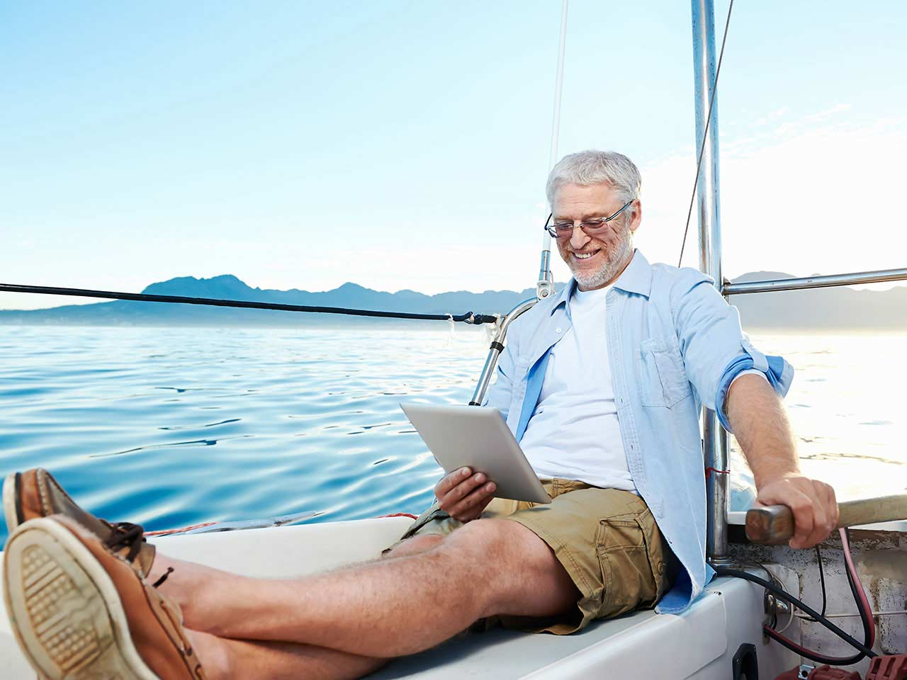 Happy man reading tablet on boat