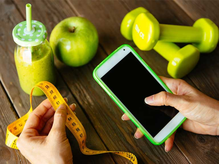 Smartphone next to a tape measure and apple to represent diet and nutrition apps