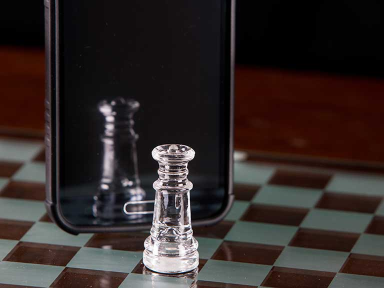 A chess piece reflected in the screen of a smartphone to represent playing traditional games on your phone as an app