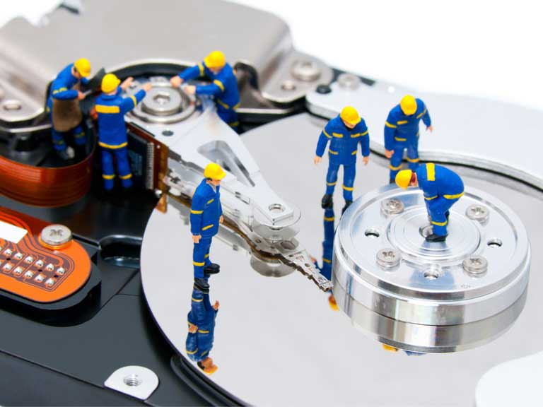 Group of small model figures mending a hard drive