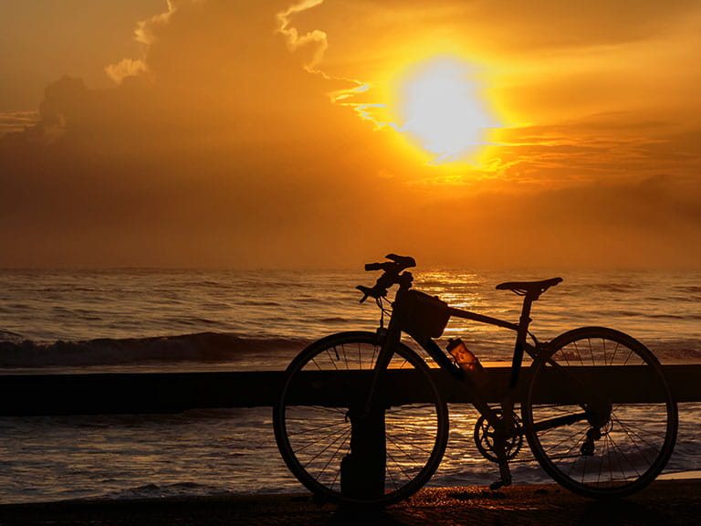 A bike left by the seaside at sunset