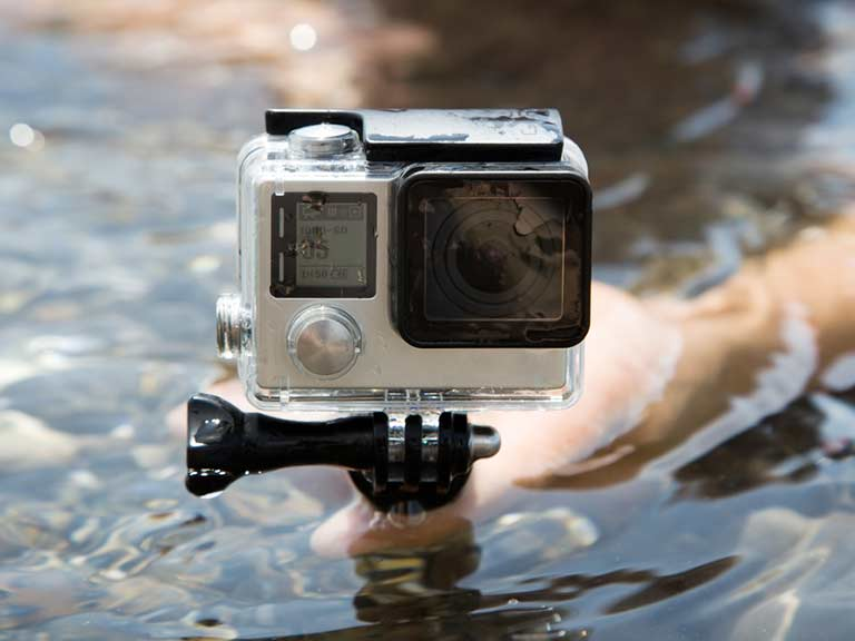 A GoPro on a tripod perches above the surface of the water