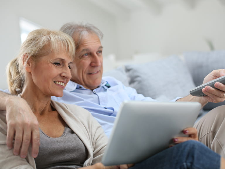 Couple watching the TV and looking at a laptop