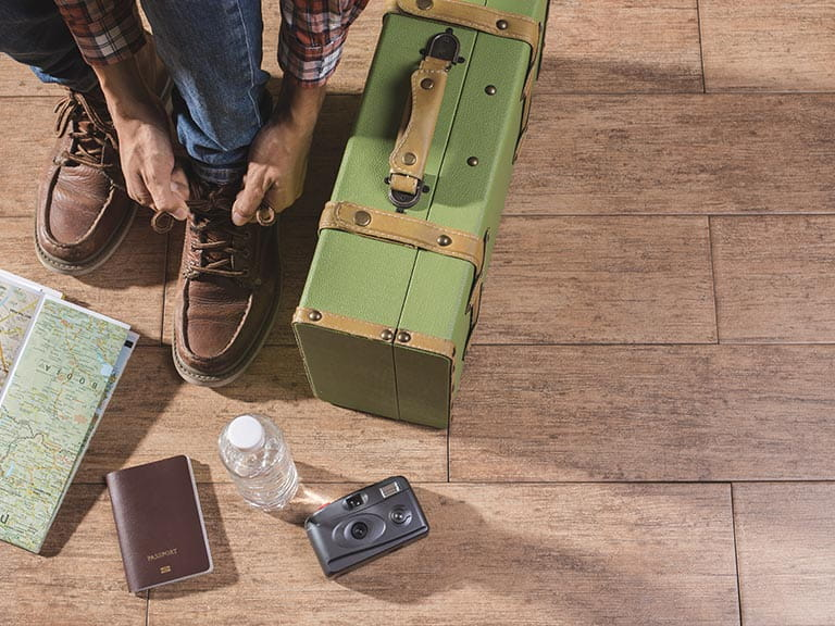A man ties his shoelaces next to a perfectly packed suitcase