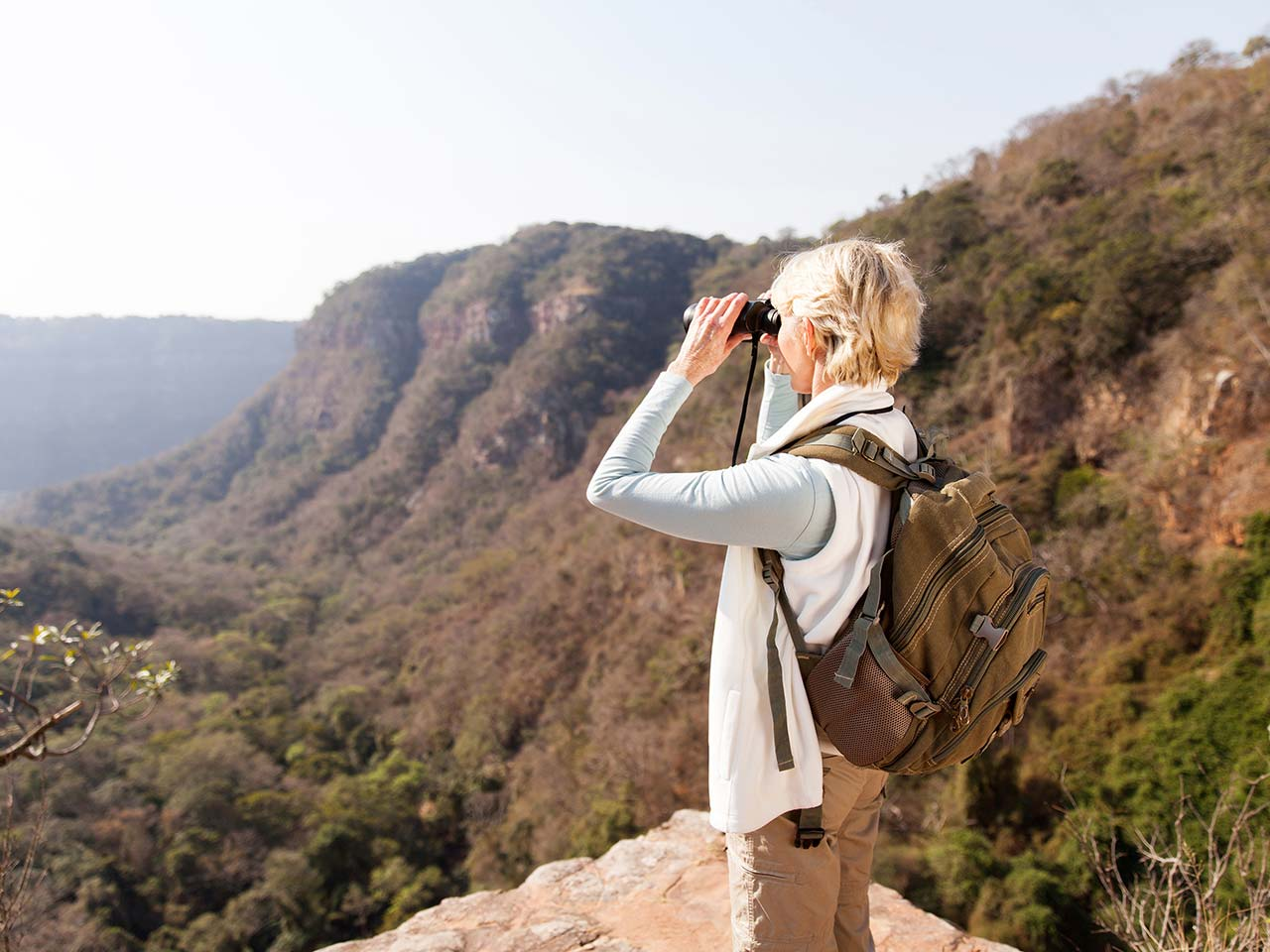 Mature woman using binoculars out hiking