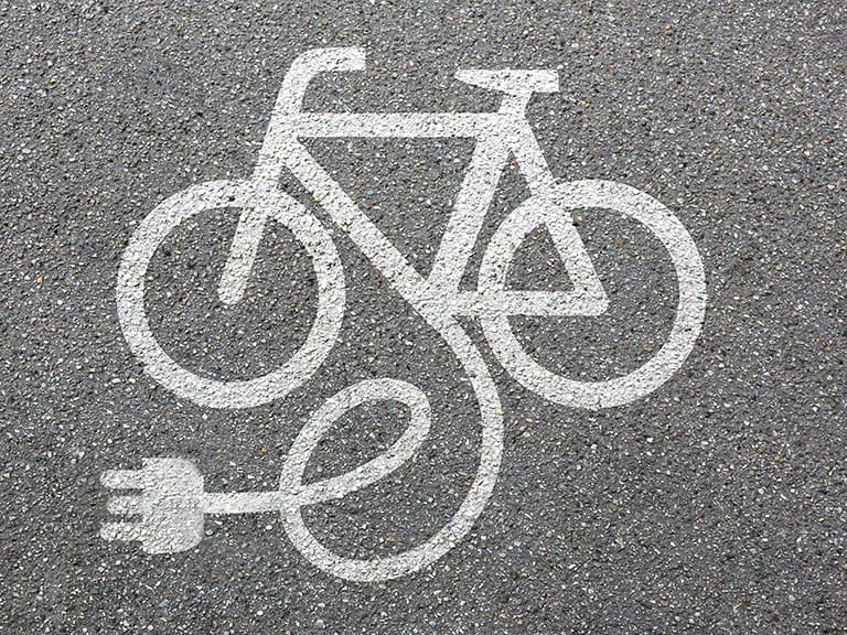 An image of a bicycle sign on a bike path with a plug to signify an electric bike