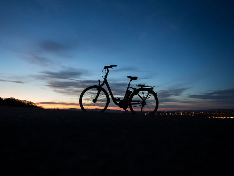 An electric bike (or e-bike) stands silhouetted against the sunset