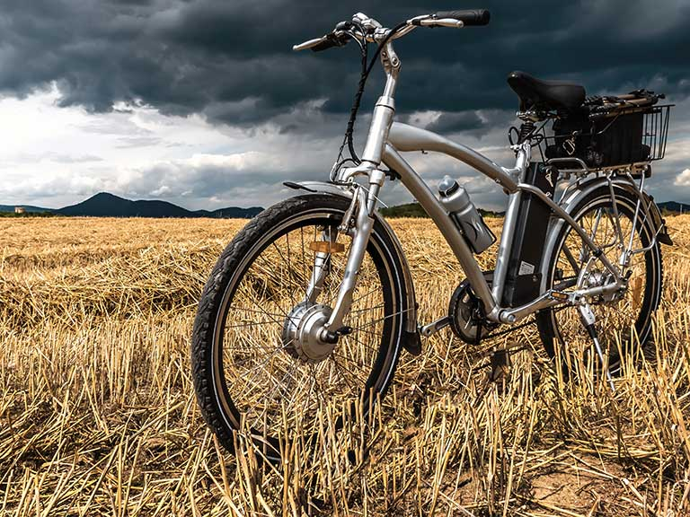 An electric bike stands in a cornfield in front of a stormy sky
