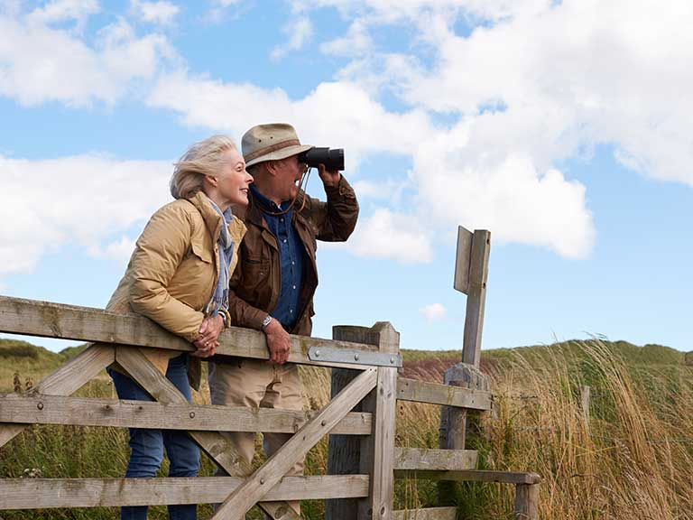 An older couple enjoy birdwatching with image stabalising binoculars