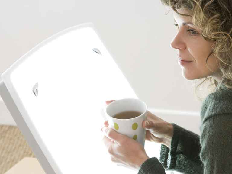 Woman sat in front of light therapy box, holding a cup