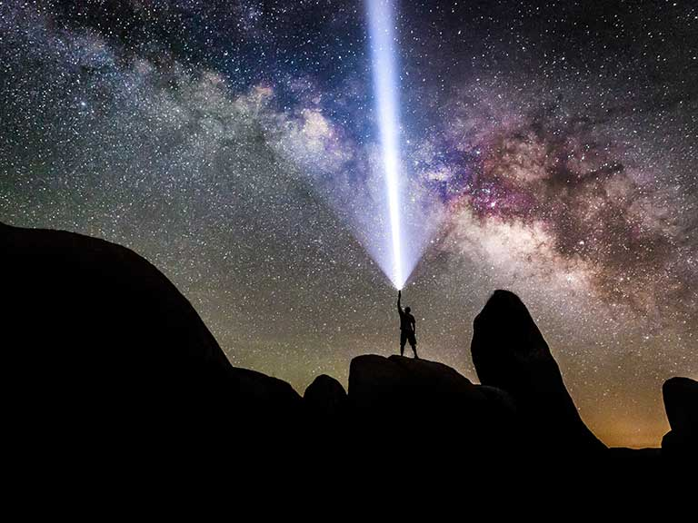 A man shines a superbright torch up at the stars