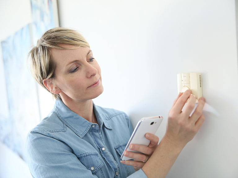 A woman connects her thermostat to her phone using Nest