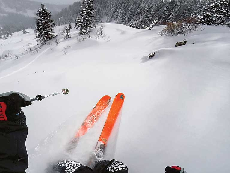 A skier uses a GroPro camera to record the downhill run
