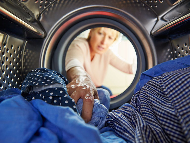 Woman checking if washing is dry in washer-dryer