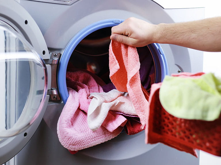 Man checking if washing in machine is dry