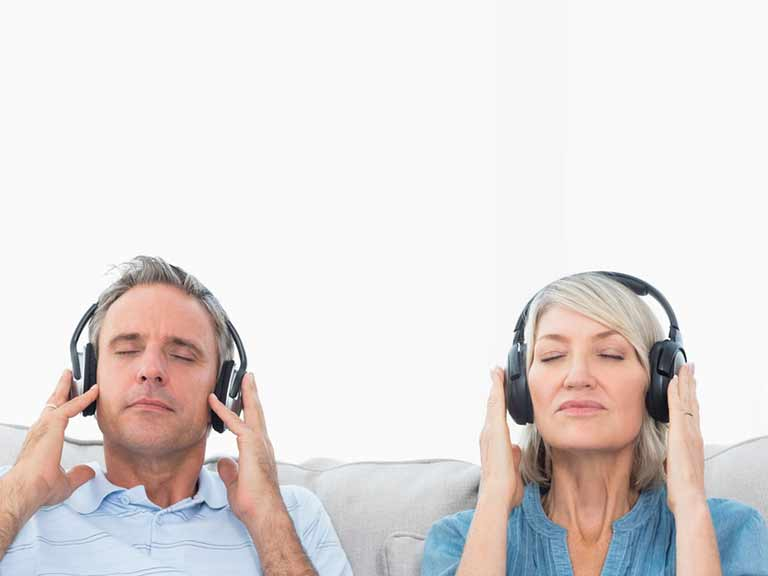 An older couple listen to music on headphones