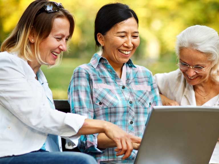 Three ladies looking at a laptop together