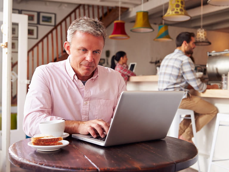 Man using public wi-fi hotspot in  a cafe