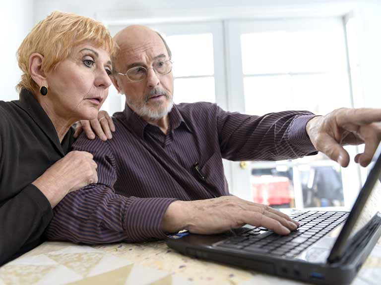 An older couple read articles online