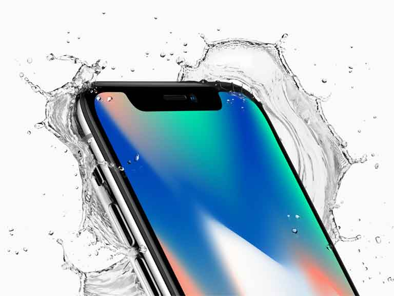 iPhone X mobile phone being splashed with water to demonstrate its water resistance