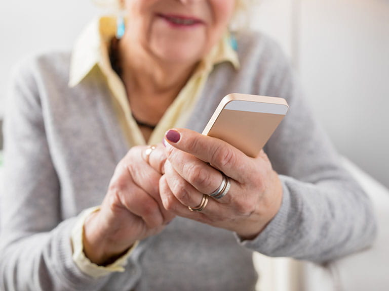 An older woman types on an iPhone
