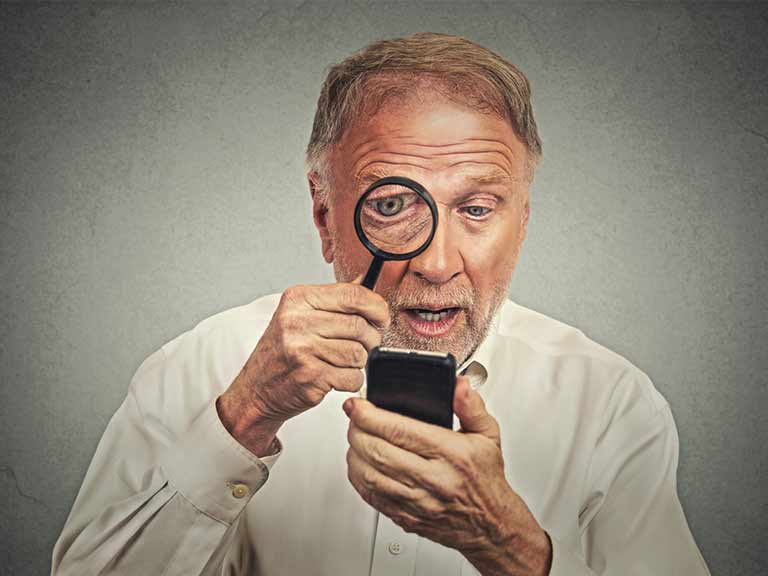 A man uses a magnifying glass to read his smartphone screen