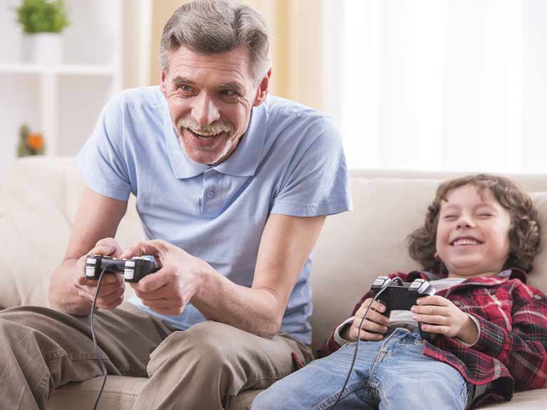 A man playing video games with his grandson